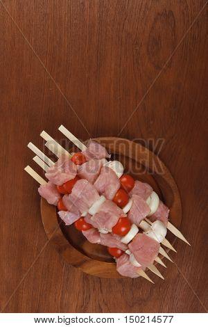 fresh raw meat fillet shish kebab turkey pork pink on skewers tomatoes mushrooms on wooden dish on big wood table