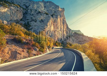 Asphalt road. Colorful landscape with beautiful mountain road with a perfect asphalt. High rocks blue sky at sunrise in summer. Vintage toning. Travel background. Highway at mountains