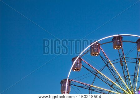 Part of Ferris wheel on blue sky background in the evening hour