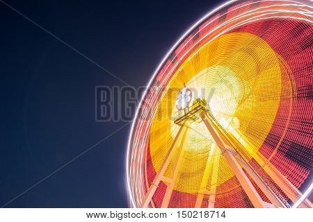 Glowing Night Illuminated Ferris wheel at an amusement park on background blue sky
