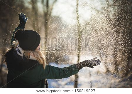 Portrait of young woman throwing the snow outdoors. Smiling girl walking in a winter park and having fun on a cold sunny day.