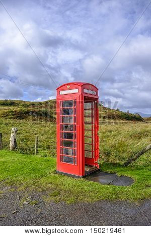 Red telephone box without a door in a remote rural location on the Isle of Skye Scotland portrait format