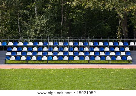 Empty blue and white seats in a football or soccer stadium. Grass field and plastic chairs open door sports arena.