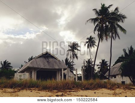 Tropical bungalow and old houses on untouched sandy beach with palms trees at stormy sunset cloudy sky Maenam beach Koh Samui Thailand