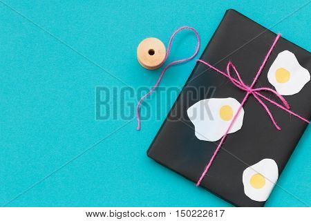 Top view on cute present wrapped in black paper and decorated with eggs shapes on balck background with scissors and pink ribbon. Funny gift for birthday party or any celebration. Holidays concept.