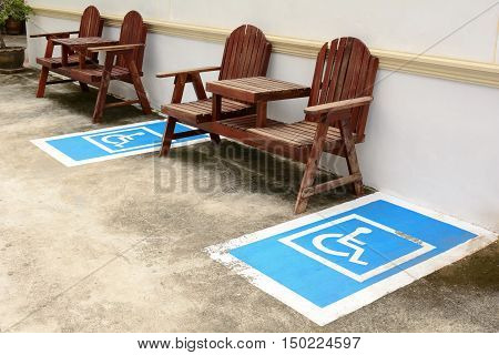 Wheelchair disabled parking area between two wooden chairs.
