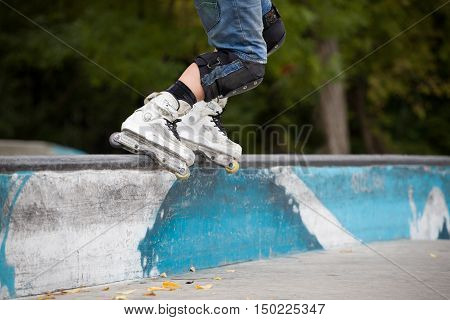Closeup of teenager's rollers on the edge of parapet. Child performing stunts on roller skates. Sport and leisure concept