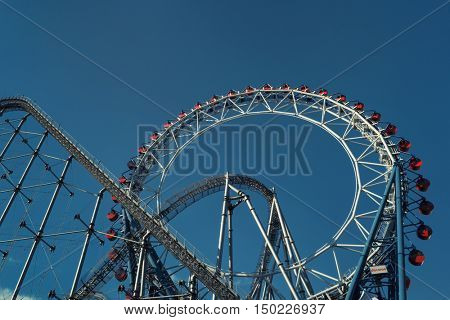 Tokyo - May 2016: Ferris wheel and rollercoaster at Tokyo Dome amusement park.