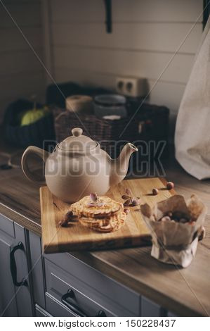 Tea pot and cookies in rustic grey kitchen interior. Slow living in country house concept. Cozy morning at home