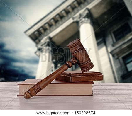 Gavel with books on courthouse background