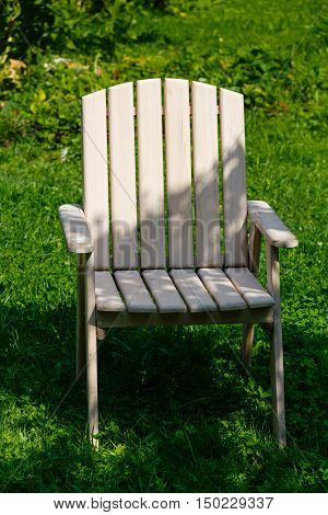 Wooden chair from a set of garden furniture on a green lawn