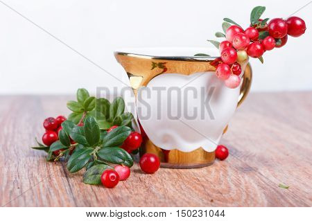stylish coffee cup and red lingonberries on wooden surface and white background