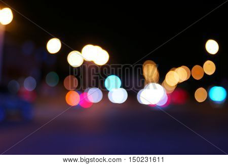 Vintage toned blurred street and car lights, urban abstract night time background with copyspace above and beneath.