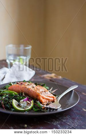 Roasted salmon or trout with chard leaves salad and onion in a plate, selective focus