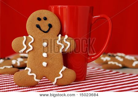 Smiling gingerbread man with red funnel mug. Additional cookies in soft focus in the background