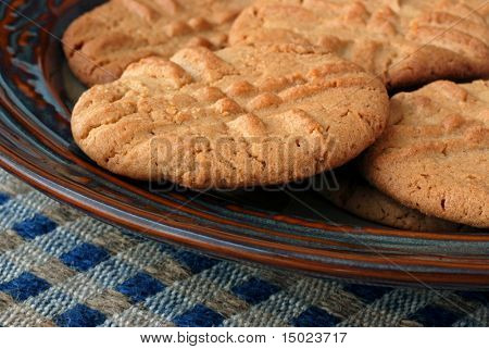 Closeup of freshly baked peanut butter cookies on a decorative ceramic plate. Shallow dof