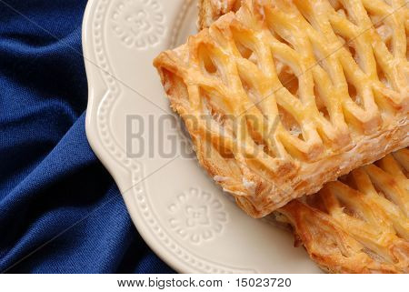 Closeup of apple danish on decorative ceramic plate with blue satin napkin as background
