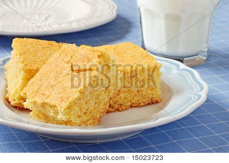 plate of freshly baked cornbread with glass of milk on blue and white tablecloth
