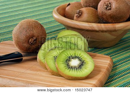 Still life image of sliced kiwi fruit on bamboo cutting board with knife.  Bowl of additional kiwi fruit on green striped cloth in the background.  Shallow dof