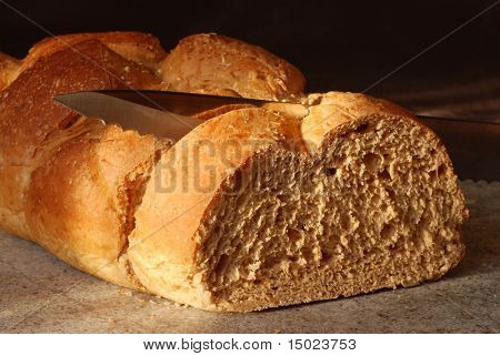 Close-up image of sliced, 9-grain, Italian Bread with knife on cutting board in warm sunlight.