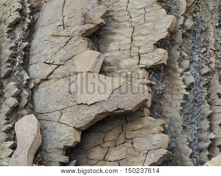 Layers of rock and sediment on the coastal rock intricately layered and destroyed