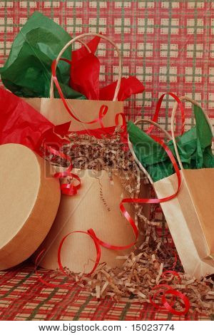 Christmas gifts in brown paper bags and boxes with green and red tissue paper and red ribbon on a sweep of plaid country style wrapping paper.