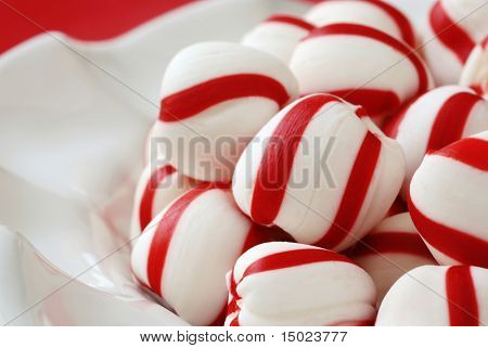 Peppermint candy sugar twists in a decorative ceramic dish with a touch of red in the background