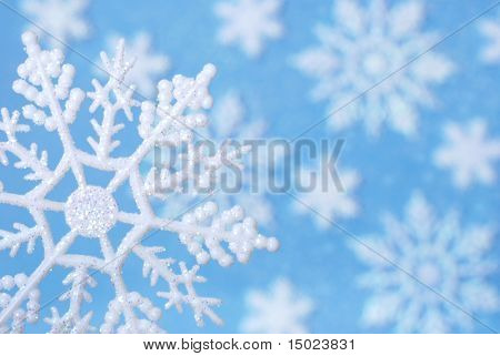 Snowflake design:  Macro image of snowflake ornament sprinkled with glitter.  Background of additional snowflakes and glitter on blue paper with shallow dof.