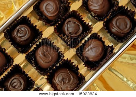 Box of chocolate cherry cordials displayed on shiny gold wrapping paper