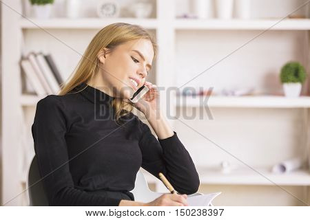 Young cute european businesswoman talking on cellular phone while doing paperwork in modern office