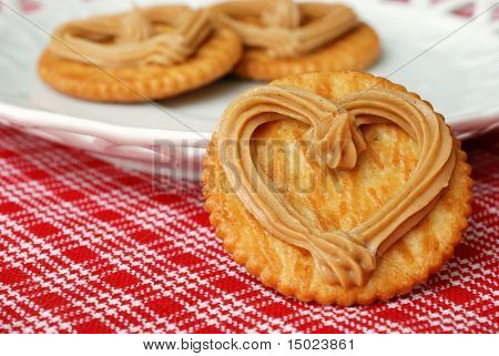 Macro image of heart-shaped swirl of peanut butter on snack cracker with additional peanut butter crackers on a plate in the background.  Shallow dof