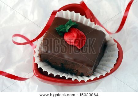 Heart shaped dish with dark chocolate petit four on white tissue paper.  Curly red ribbon added for accent.  Close-up with shallow dof.