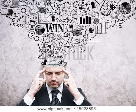 Thinking young businessman with business sketch coming out of his head on concrete background. Brainstorming concept