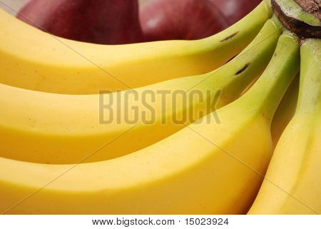 Macro abstract of banana curves with red pears out of focus in the background