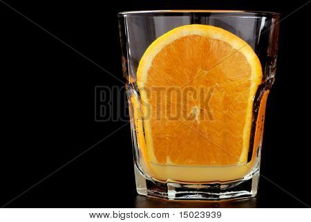 """""""freshly squeezed""""  Close-up image of a fresh orange slice squeezed into a small juice glass on a reflective black surface with black background."""