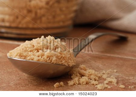 Macro still-life of serving spoon overflowing with brown sugar onto color coordinated porcelain tile. Glass canister of brown sugar and homespun cloth out of focus in the background.  Shallow dof