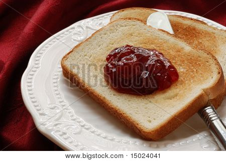 Freshly toasted bread with cherry preserves and serving knife on a decorative, antique plate.  Red damask table linen in the background.