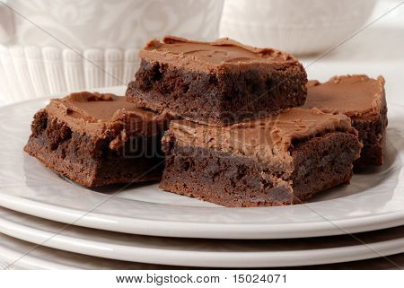 Chocolate frosted brownies on a ceramic plate with matching pitcher and dish in the background.  Shallow dof