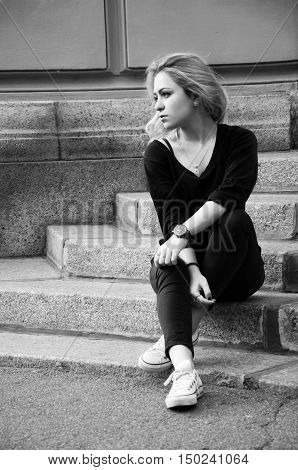 Young woman with blond hair wearing dark pants and sweater sitting on the stairs waiting for someone alone. Street style.Black and white photo.