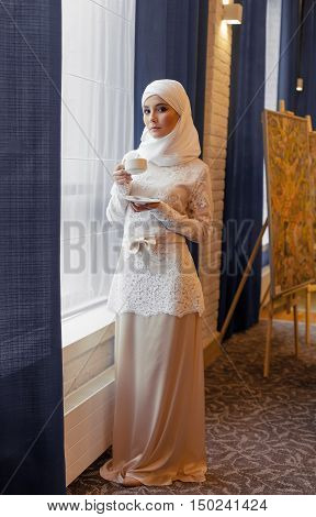 beautiful Muslim woman in a white wedding dress standing at window in hotel