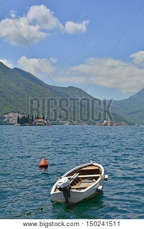 An old wooden boat in the harbour of the historic Montenegrin town of Perast. The islands of Our Lady of the Rock and St George's Abbey can be seen in the distance