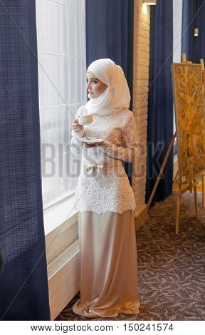 Muslim woman in a white wedding dress with a cup of tea in his hands in a hotel