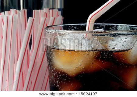 Retro image of cola on ice with old-fashioned straw dispenser.  Macro with shallow dof.  Bubbles are inherent in the glass