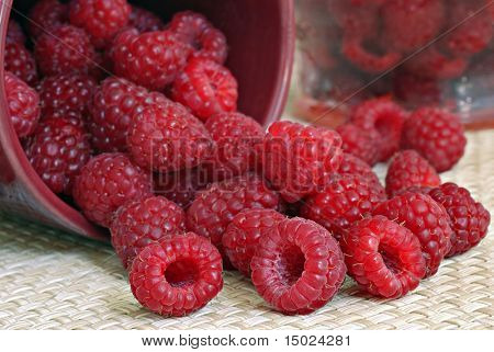 Fresh raspberries spilling out of a small ceramic dish onto a woven placemat.  Additional berries in a glass container visible in the background.  Macro still-life with shallow dof.