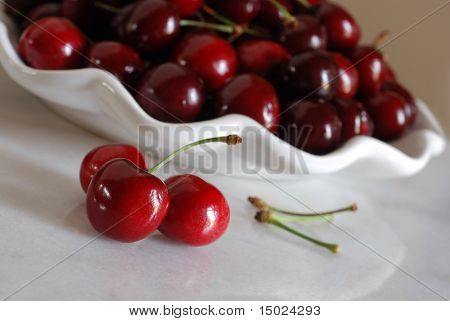 Fresh bing cherries reflecting on a shiny marble table with decorative bowl of cherries in the background.  Tilted composition with extremely shallow dof.  Main focus on the front cherry.