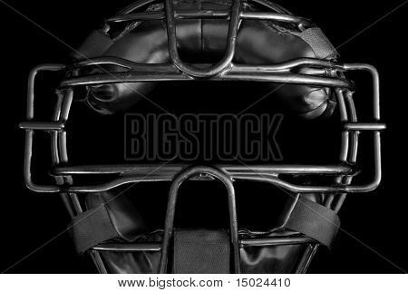 Umpire mask in black and white.  Close-up of well worn, baseball umpire mask on black background.