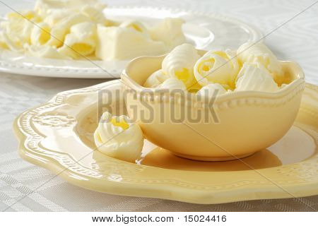 Creamy butter curls in a decorative dish with bits and pieces of stick butter visible in the background.  Close-up with extremely shallow dof