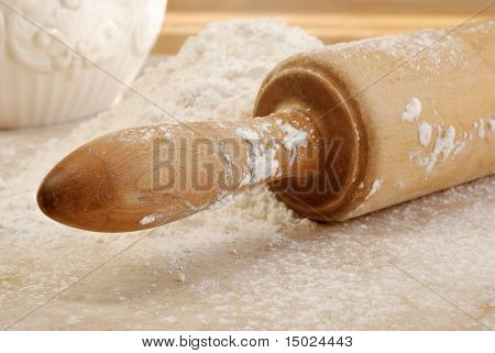 Vintage wooden rolling pin with flour on sunlit countertop.  Close-up with selective focus on handle.  Shallow dof.