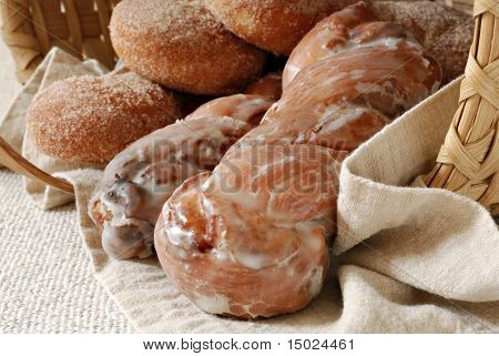 Freshly baked pastries spilling out of a handwoven basket with natural cotton linens.  Close-up with shallow dof