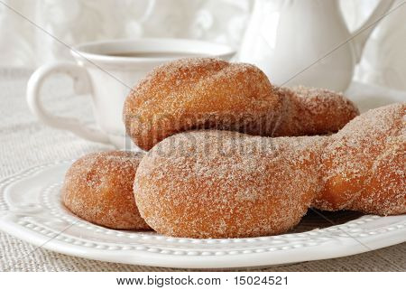 Freshly baked cinnamon twist pastries with hot beverage and elegant lace in the background.  Close-up with shallow dof.